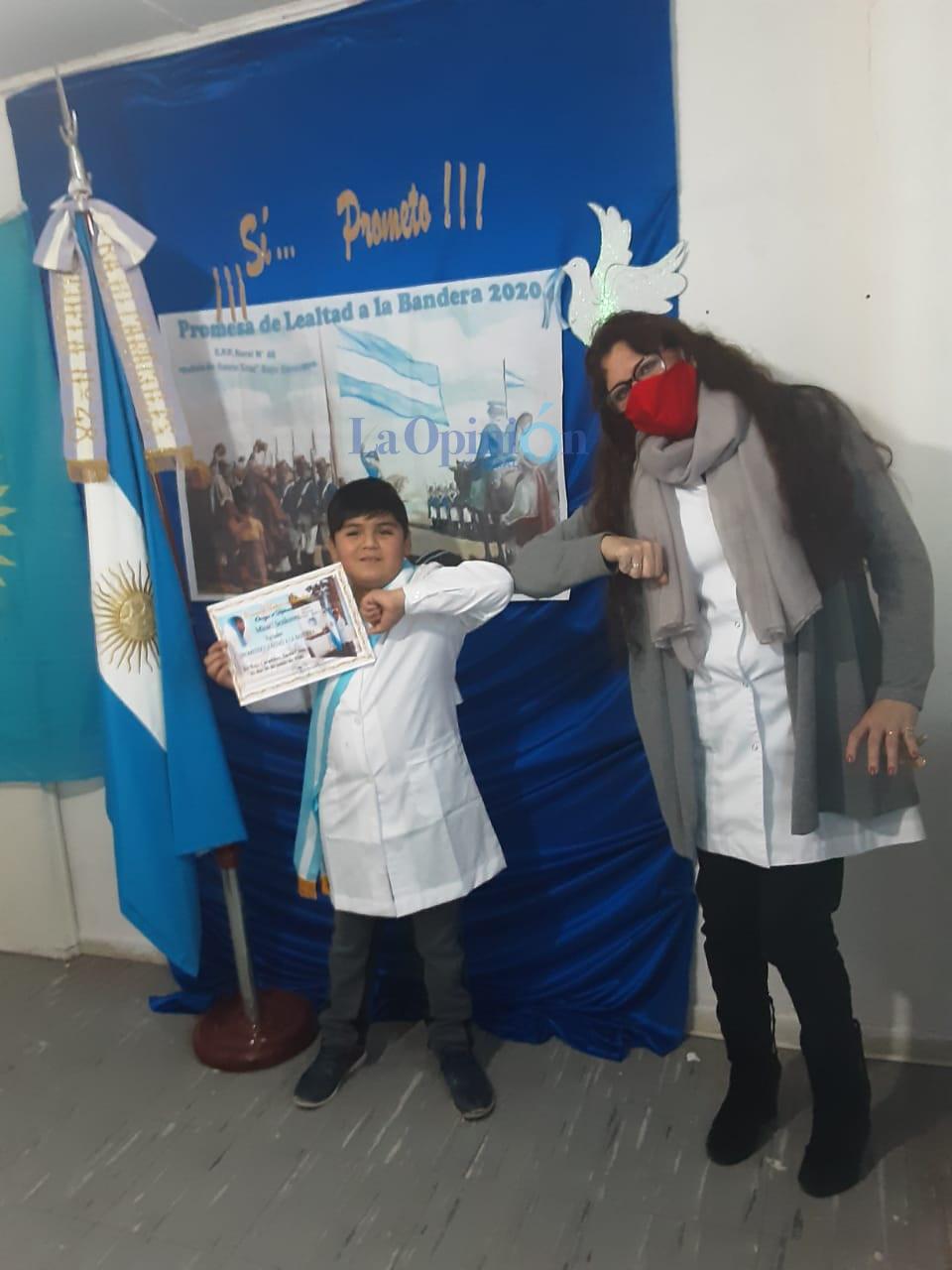 Misael se saluda con la directora de la Escuela rural Primaria 48 de Bajo Caracoles, Gloria Villanueva, tras la promesa a la bandera con el presidente Alberto Fernández.