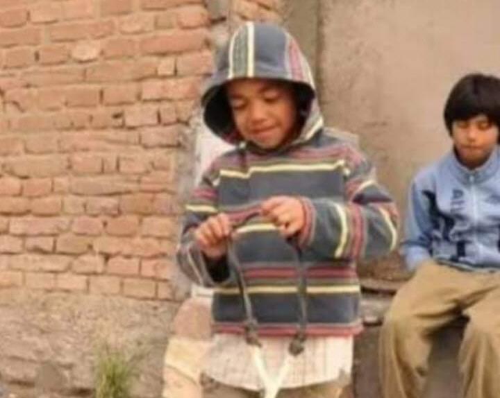 Juan de niño jugando con una gomera.