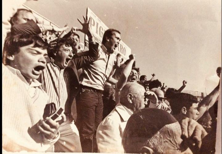 FOTO EXCLUSIVA. Alfredo Serra (en el centro) y Mario Fahsbender (a su izquierda) gritan un gol de Platense. Tablones de madera y 'pasión calamar'.