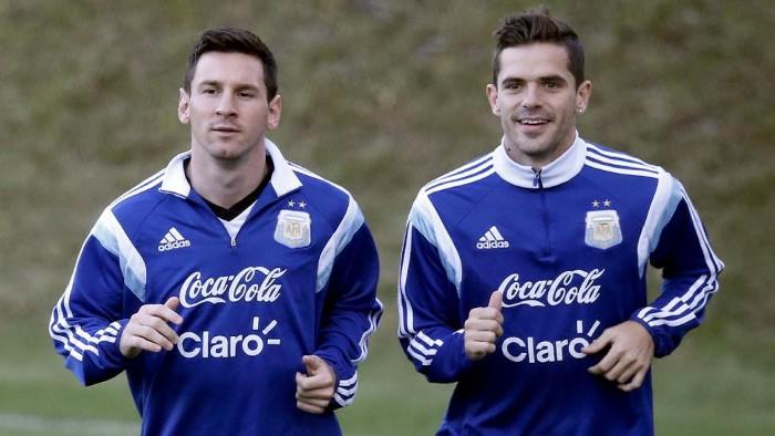 Lionel Messi y Fernando Gago trotando juntos.