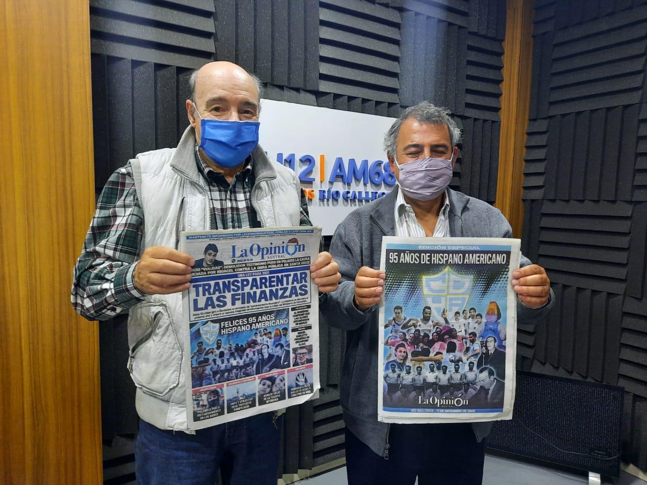 El presidente del Club Hispano Americano, Jorge Castro, y el conductor radial Carlos Zapico, durante el especial de LU12 por el aniversario del Celeste. Ambos con las tapas de La Opinión Austral en homenaje al club.