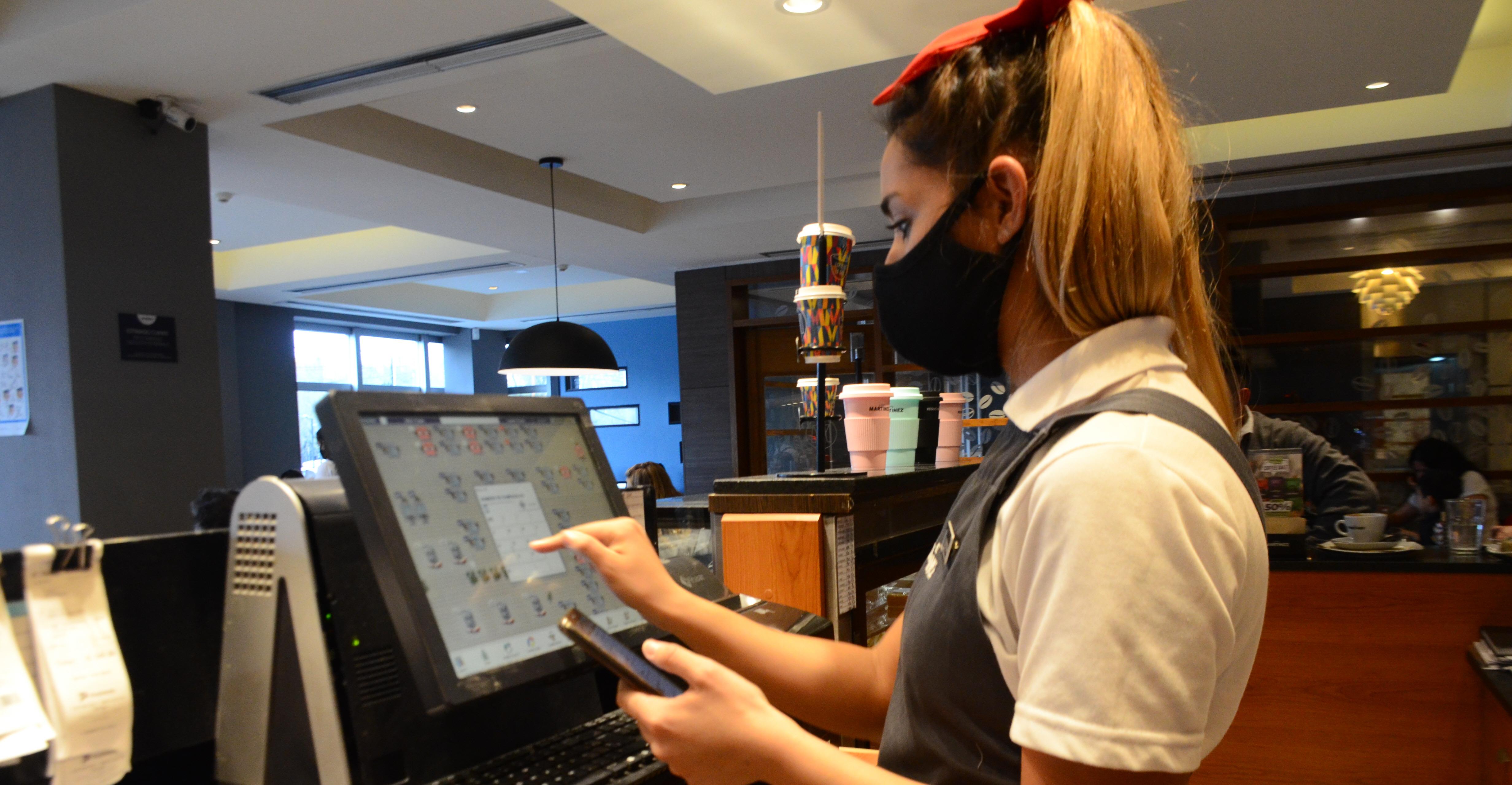 Florencia recibe pedidos para delivery en una cafetería local.